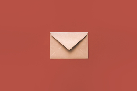 Christmas craft envelope on red isolated background.