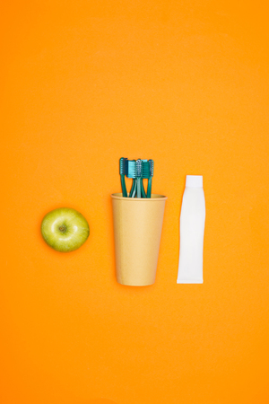 Top view of apple, toothbrushes in a paper cup and tube of toothpaste