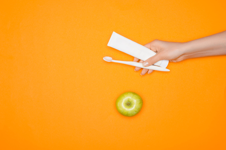 Woman holding toothbrush and tube of toothpaste, isolated on orange with apple