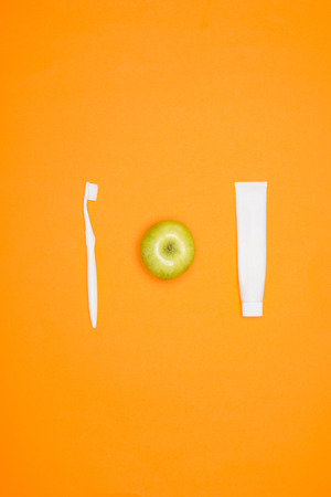 Toothbrush, apple and tube of toothpaste, isolated on orange Stock Photo