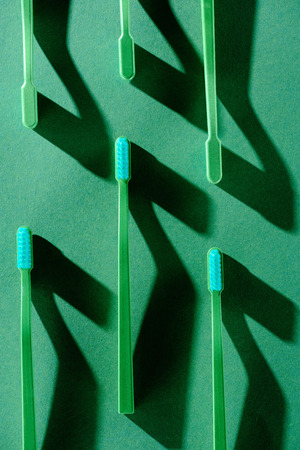 影の緑の歯ブラシを持つミニマルな背景