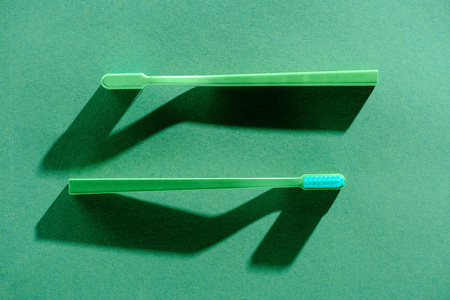 Two green toothbrushes, on green