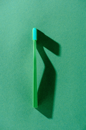 One green toothbrush with shadow on green isolated background.