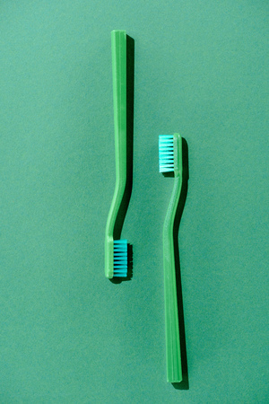 Green toothbrushes on green isolated background.