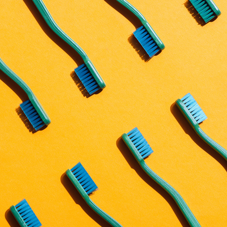 Green toothbrushes on yellow isolated background.