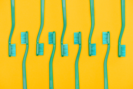 Minimalistic background with green toothbrushes in row Фото со стока