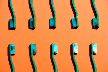 Green toothbrushes on orange isolated background. Фото со стока