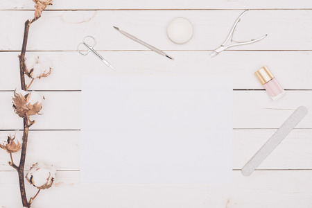 Manicure tools and white paper on wooden table 스톡 콘텐츠