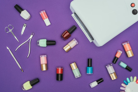 Top view of nails polishes and UV lamp