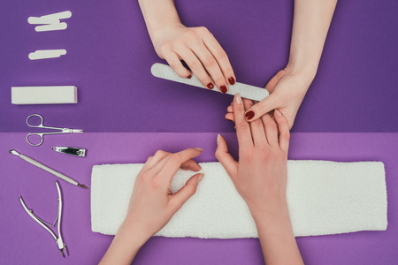 Manicurist filing nails with nail file 스톡 콘텐츠