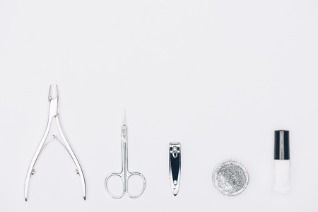 Top view of nail nippers, scissors and glitter