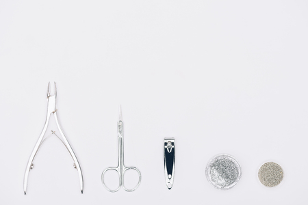 Top view of nail nippers, scissors and different glitter