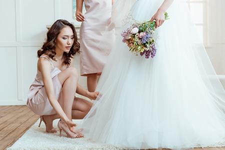 bridesmaid preparing bride for ceremony Stock Photo