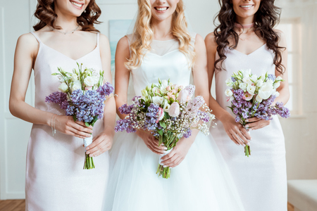 bride with bridesmaids holding bouquets