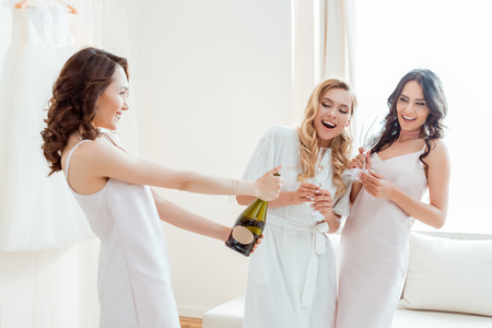 bride with bridesmaids opening champagne bottle