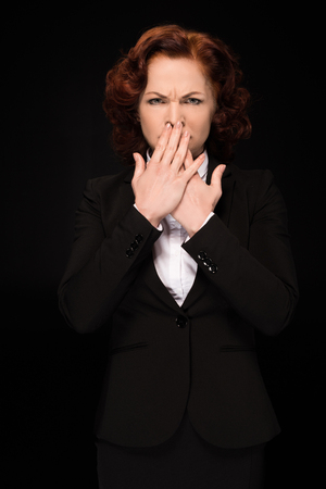 Businesswoman covering mouth Stockfoto