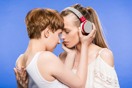 Lesbian couple hugging and listening to music Stock Photo