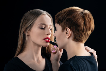 Woman applying lipstick onto girlfriend Stock Photo