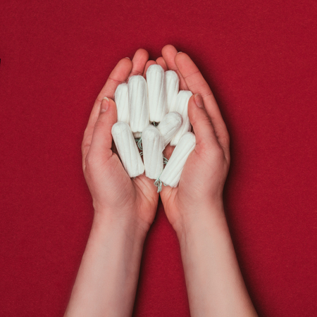 partial view of woman holding tampons in hands