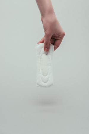 partial view of woman holding menstrual pad in hand Stock Photo