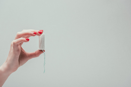 cropped shot of woman holding tampon in hand