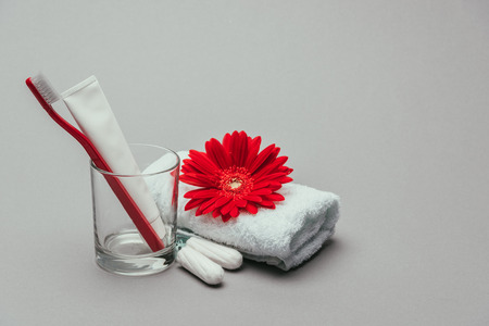 hygiene supplies, flower and towel isolated on grey