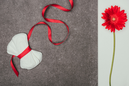 arranged menstrual pads with ribbon and red flower on grey surface