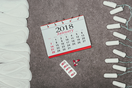 arranged menstrual pads and tampons, calendar and pills on grey surface Stock Photo