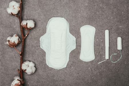 top view of arrangement of cotton twig, menstrual pads and tampons