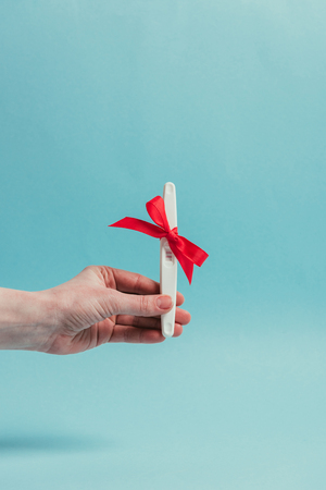 cropped shot of woman holding pregnancy test with ribbon
