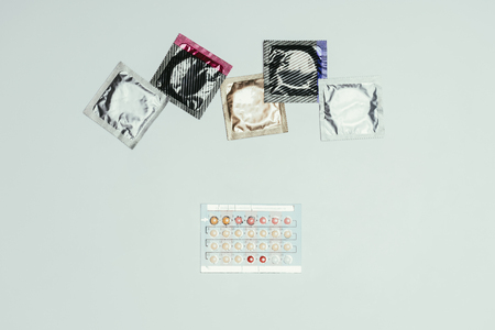 top view of arranged condoms and contraceptive pills