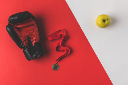boxing glove with medal and apple on red and white surface