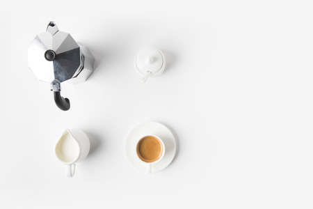 top view of arranged cup of coffee, jag of milk and coffee maker