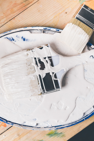 brushes in white paint on cover from bucket Banco de Imagens