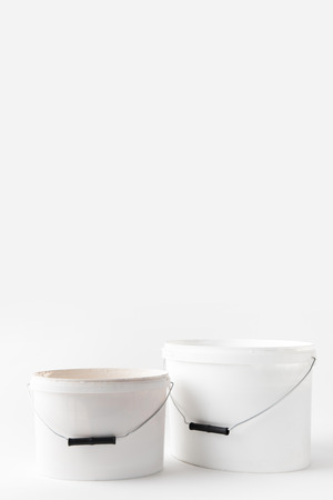 two plastic white buckets with paints