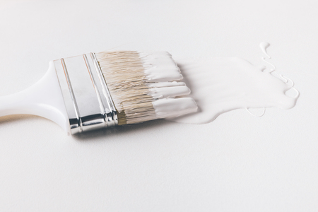 one paint brush in white paint on surface