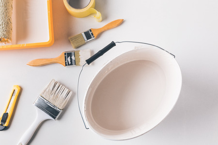 top view of bucket with white paint and tools for repairs