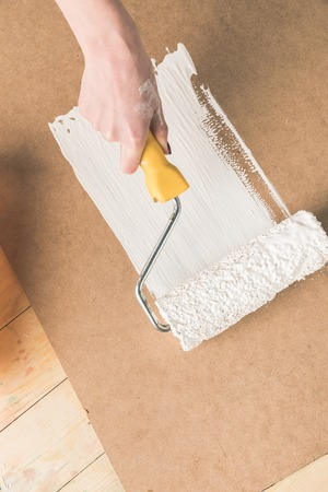 woman painting plywood with paint roll brush