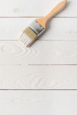 brush in white paint on painted wooden surface
