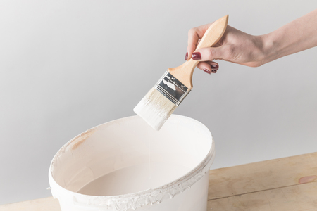 woman holding brush in white paint above bucket Banco de Imagens