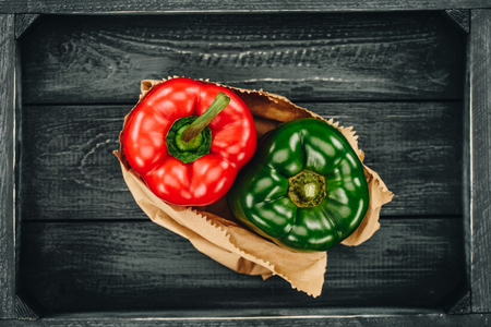 red and green bell peppers in shopping paper bag