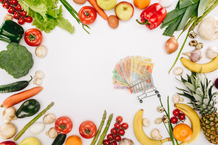 top view of shopping cart with cash between vegetables and fruits Stock Photo