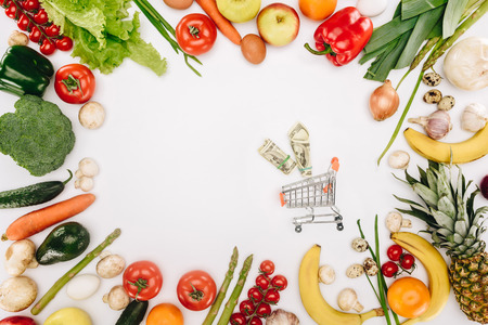 top view of small shopping cart with dollars between vegetables and fruits Фото со стока - 95170427