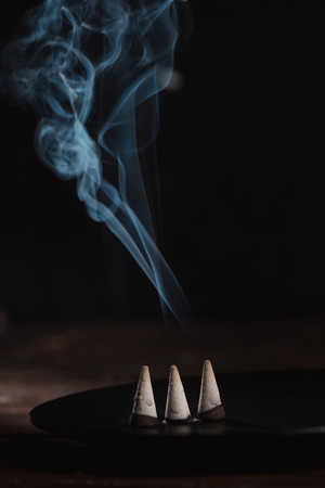 burning incense sticks with smoke on table