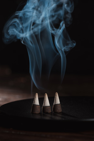 three burning incense sticks with smoke