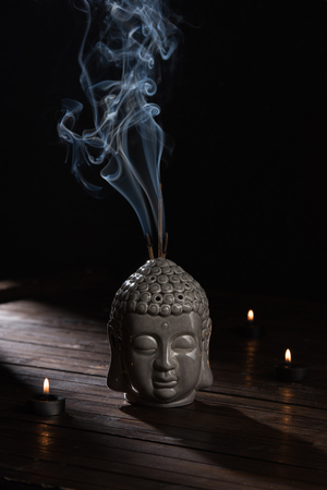 sculpture of buddha head with burning incense sticks and candles Banco de Imagens