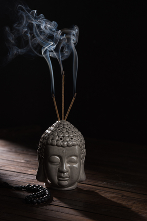 buddha head with burning incense sticks Foto de archivo