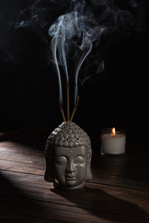 sculpture of buddha head with burning incense sticks and candle