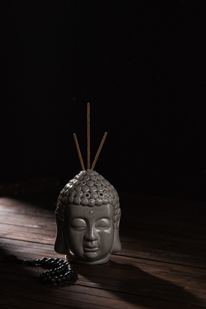 buddha head with incense sticks on wooden table Stock Photo
