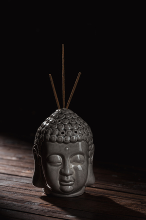 buddha head with incense sticks Stock Photo